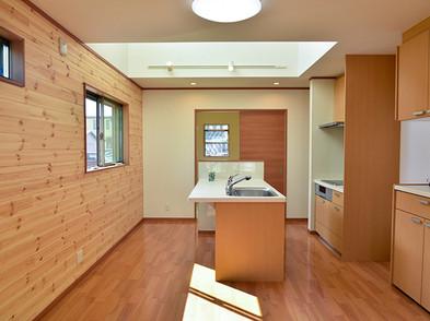 吹抜けで明るいLDKは 天然赤松の壁板。キッチン収納も付いています