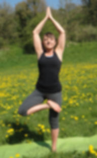 Lucia in tree pose in a meadow at Stowford