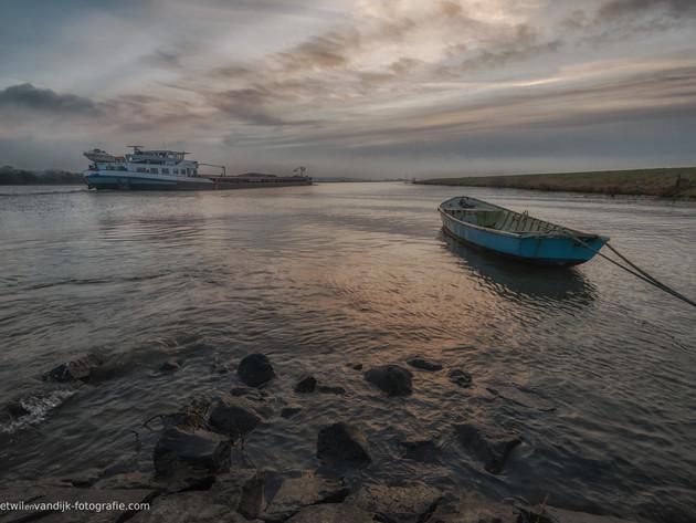 Binnenvaartschip en roeiboot op de Nederrijn