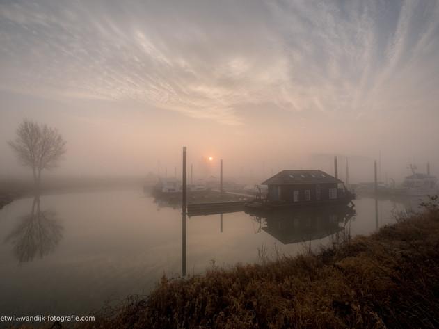 Zonsopkomst met mist bij boothuis haven Maurik