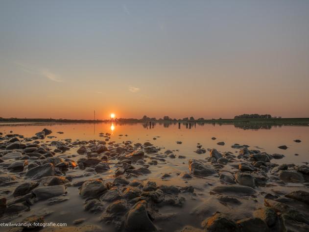Stenen bij rivier De Lek tijdens zonsondergang