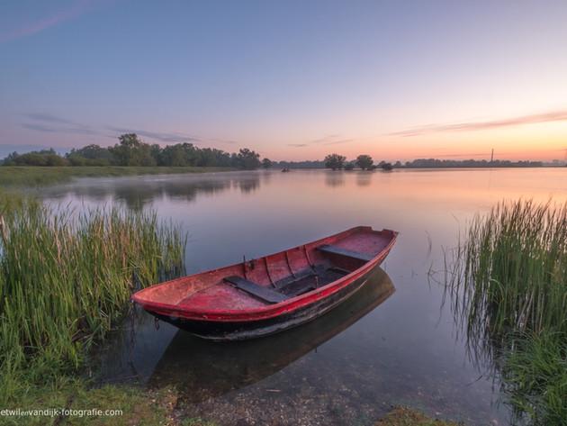 Roeiboot op waterplas bij zonsopkomst