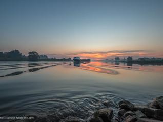 Binnenvaartschip op de Lek bij Ravenswaaij tijdens prachtige zonsopkomst