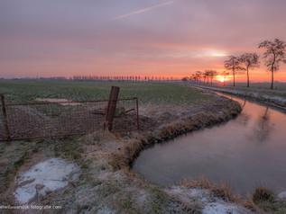 Winters landschap bij zonsopkomst