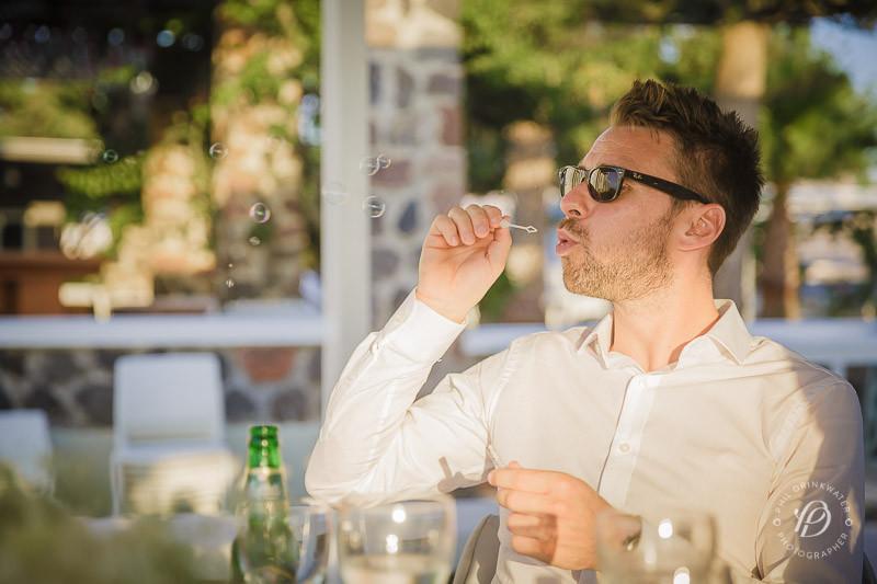 Man attending wedding blowing bubbles