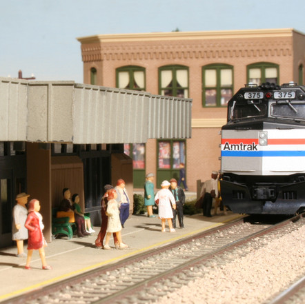 Amtrak locomotive #375, a F40PH, pulls into the passenger station in North Hawksridge. This section of the layout is also used on a modular club layout.