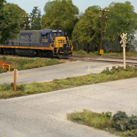 A local freight lead by CSX locomotive #3126, a GE B23-7, passes through a grade crossing in North Hawksridge. This portion of the layout is built on a removable modular frame.