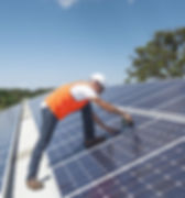 A man in an orange vest drills Solar Panels to the roof of a large industrial building on a sunny day