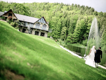 bride-groom-walking-along-grass-on-wedding-day-at-canada-lake-lodge-in-south-wales.jpg