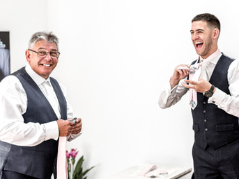 groom-doing-up-his-tie-while-laughing-with-his-father.jpg