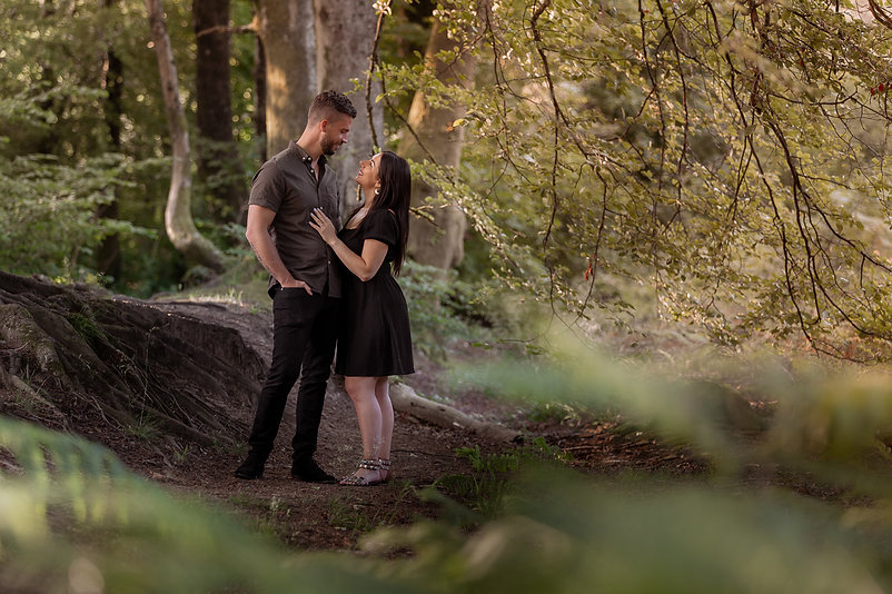 Man and woman standing in a forest during pre-wedding photoshoot in Hensol Forest, South Wales