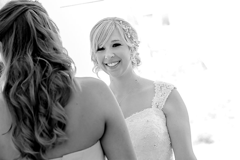 A bride smiling at one of her bridesmaids
