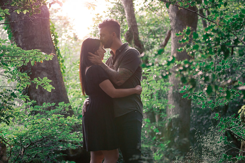 Man kissing female on the forehead while holding each other at sunset in Hensol Forest, South Wales