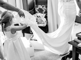 flower-girl-helping-bride-with-her-wedding-dress-at-bryn-meadows-hotel-in-south-wales.jpg