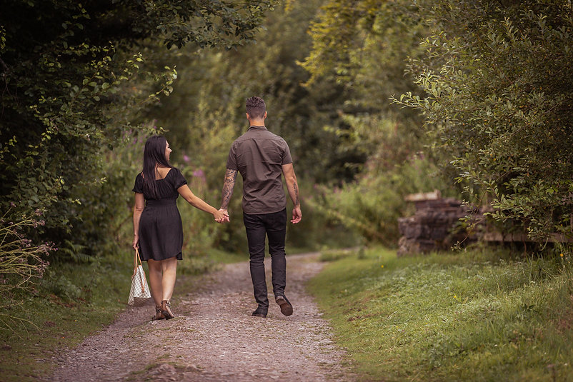 Man and woman holding hands while walking away down a pathway towards Hensol Forest in South Wales