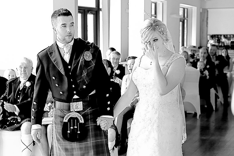 A tearful bride with her groom during their wedding ceremony at Canada Lodge and Lake near Cardiff, South Wales