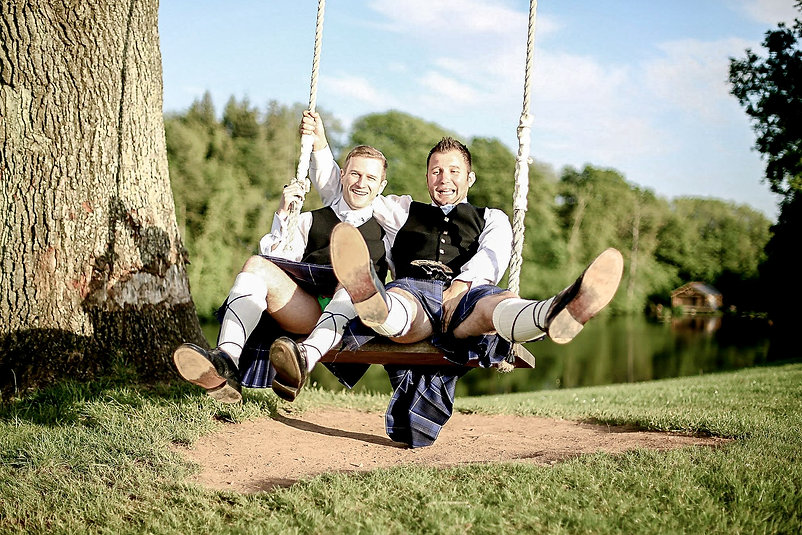Two groomsmen wearing kilts having fun on a large swing at sunset on the grounds of Canada Lodge and Lake near Cardiff, South Wales
