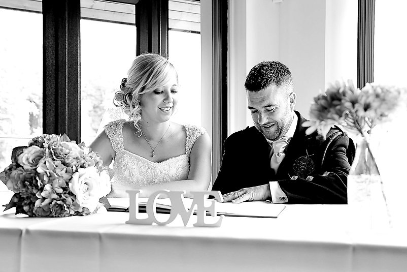 A bride smiling while her happy husband signs the register following the ceremony on their wedding day at Canada Lodge and Lake near Cardiff, South Wales