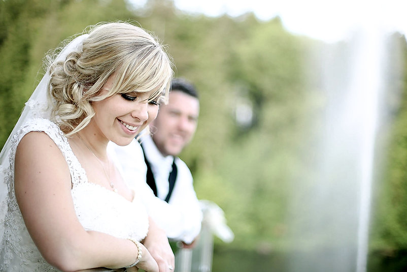 A bride smiles while looking down from a balcony with her husband behind her at Canada Lodge and Lake in Cardiff, South Wales