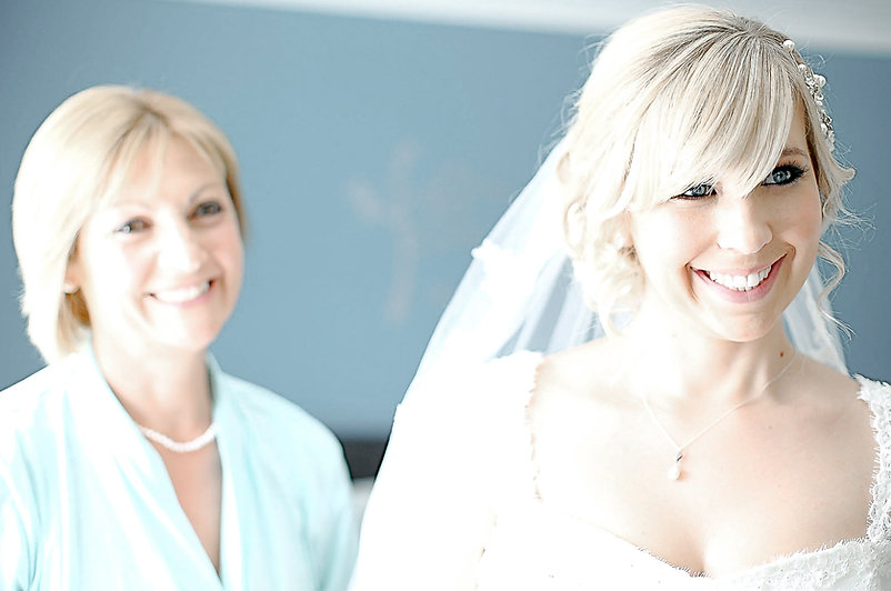 A bride and her mother both smiling on the morning of her wedding day during bridal preparations