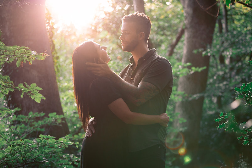 Male holds his partner passionately as they embrace at sunset in a forest during pre-wedding shoot at Hensol in South Wales