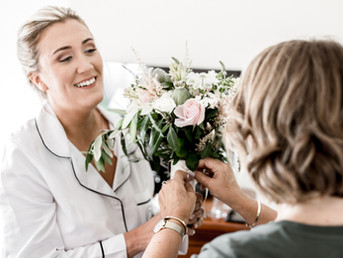 bride-laughing-with-her-mother-as-she-ties-up-bouquet-of-flowers.jpg