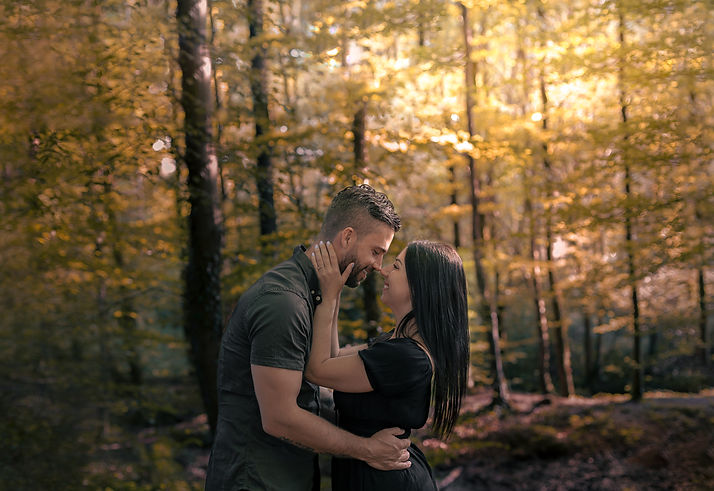 A young couple embrace each other in a forest at sunset in Hensol, South Wales