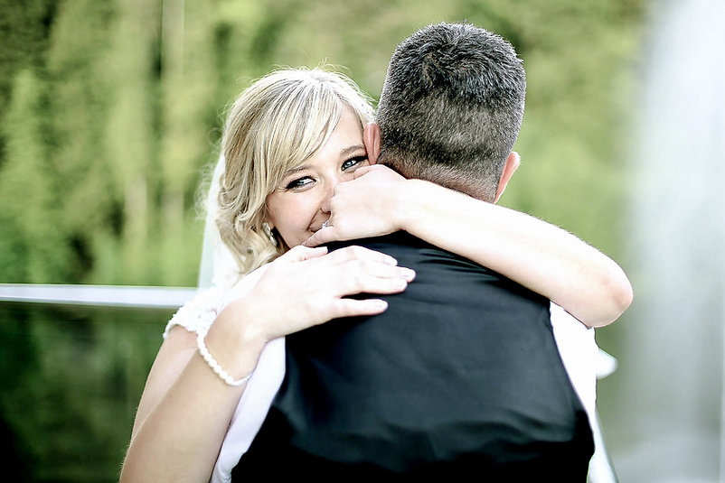 A newly-wed wife hugs her husband on their wedding day with the look of joy in her eyes on the balcony of Canada Lodge and Lake near Cardiff, South Wales
