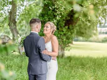 bride-and-groom-standing-smiling-at-each-other-in-forest-at-bryn-meadows-south-wales.jpg