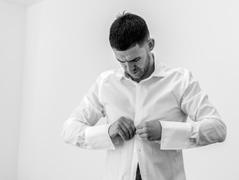 groom-buttoning-up-his-shirt-on-wedding-day-morning.jpg