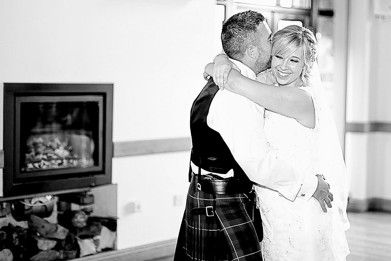A bride and her husband embrace with a hug and a smile during the first dance on their wedding day at Canada Lodge and Lake near Cardiff, South Wales