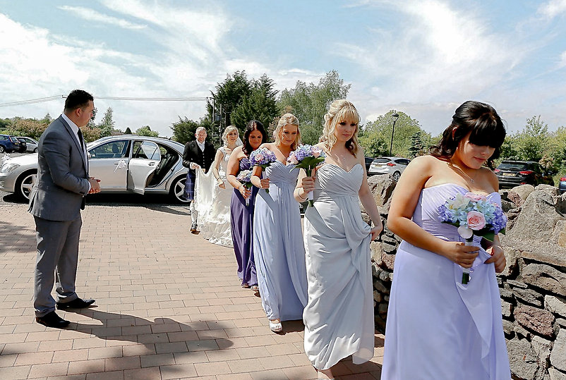 The bridal party making their way towards the ceremony after exiting the wedding car at the Canada Lodge and Lake near Cardiff, South Wales