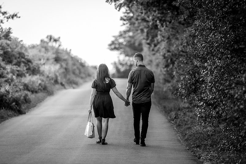 A young couple in love holding hands while they walk away down a road towards the sunset in Hensol, South Wales
