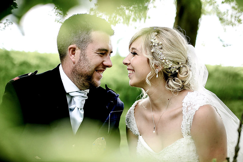 A happy bride and groom lovingly smile at each other on the grounds of the Canada Lodge and Lake near Cardiff, South Wales