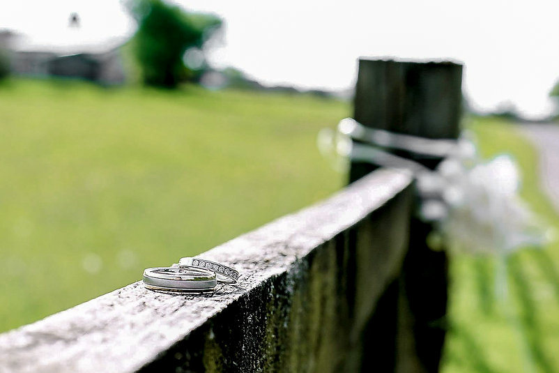 Closeup of two wedding rings displayed on a wooden fence in a field at Canada Lodge and Lake near Cardiff, South Wales