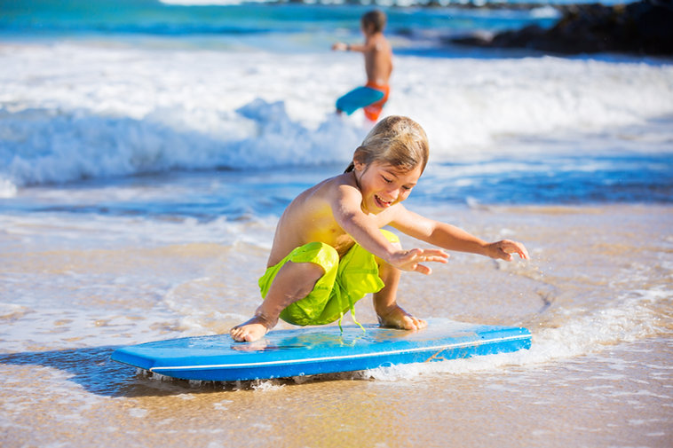 A kid has a surfing lesson and is sliding on a skimboard in Malta.