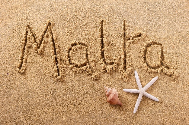 Malta written in the sand on a beach.