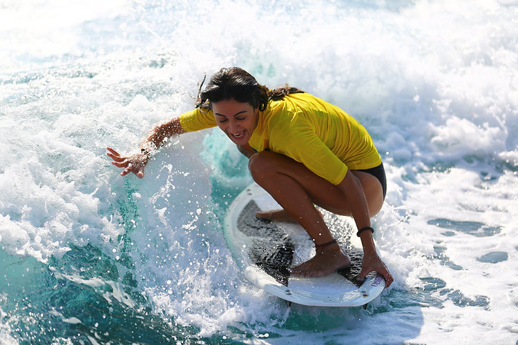 A woman is catching a wave on a skimboard in Malta.