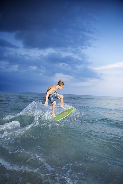 Man surfing on a skimboard on Golden Bay in Malta.