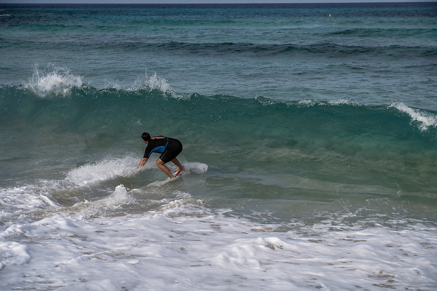 A man is surfing and turning on a wave at Golden Bay in Malta.