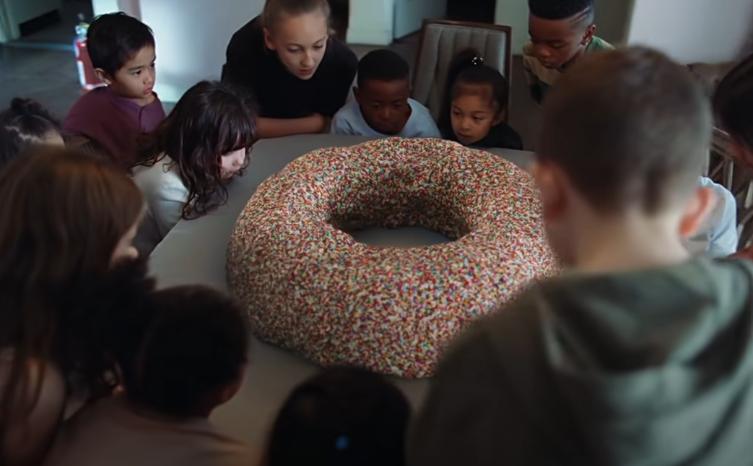 Niños frente a una gran dona con chispas en video TK de Rosalía
