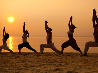 Five people practising yoga at the beach