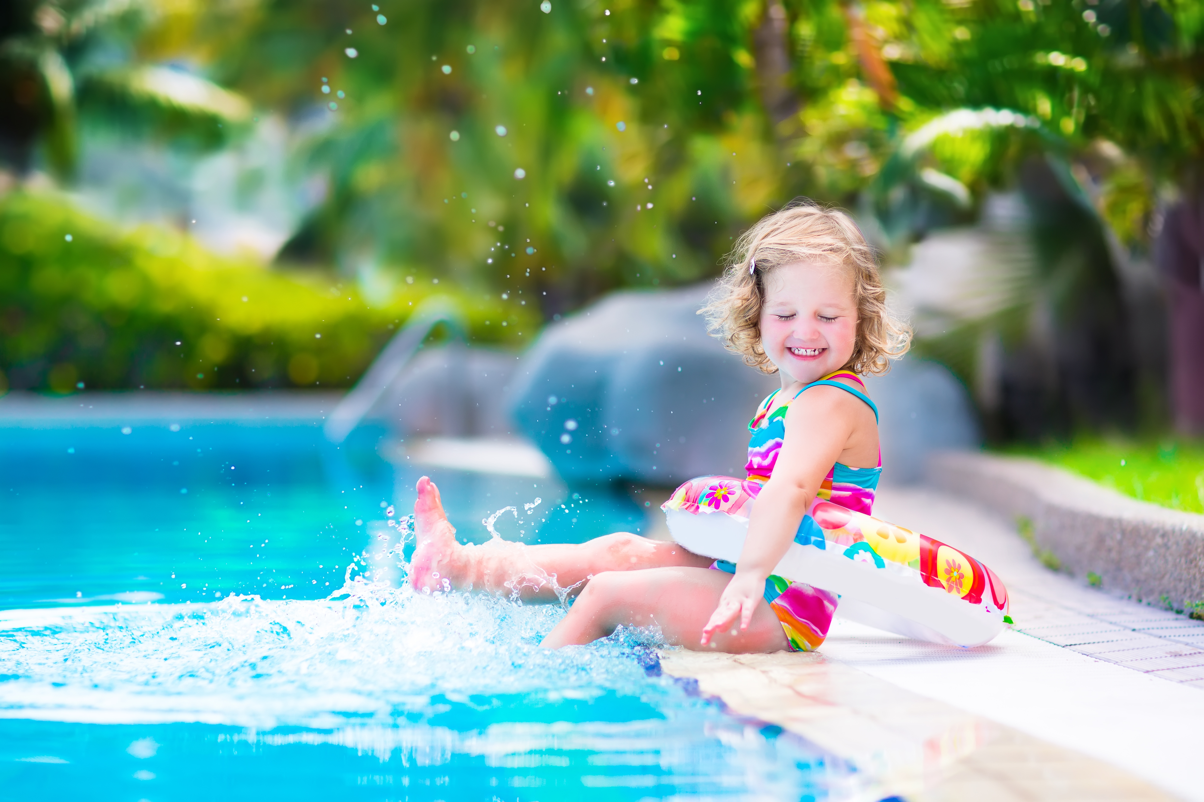 Adorable little girl with curly hair wearing a colorful swimming suit playing with water splashes at