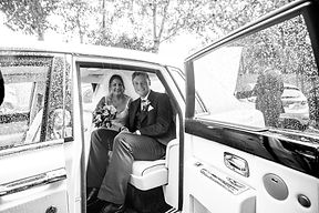Bride & Groom sit in their wedding car, waiting for the rain to stop after their wedding in Hall Green.