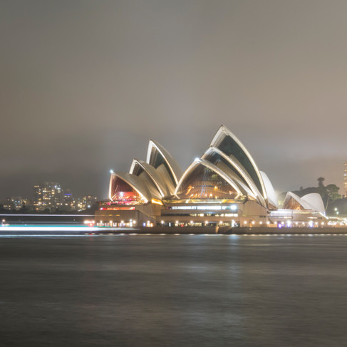 Sydney Opera House with light trails of a passing boat.