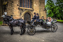 Bride and groom sit in a horse drawn carriage at St Johns Church, Bromsgrove.
