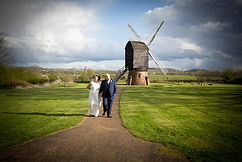 Bride and groom walk from the windmill at Avoncroft Museum, Bromsgrove.