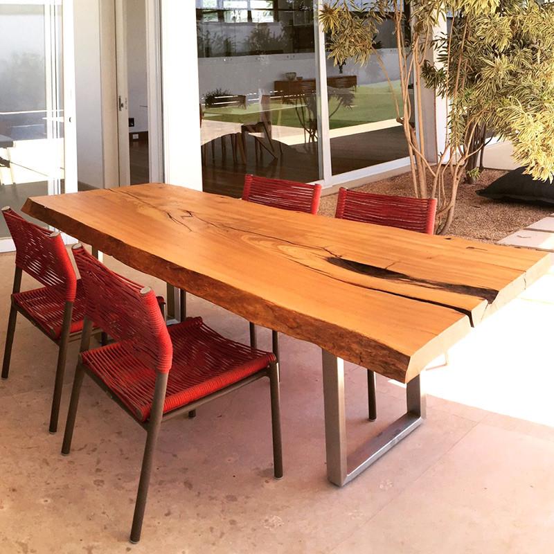 Mesa de jantar em madeira maciça com pés em inox, acompanhada de cadeiras vermelhas