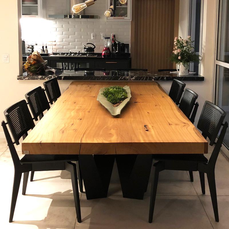 Mesa de jantar em madeira maciça com pés em aço carbono, acompanhada de cadeiras de madeira na cor preta