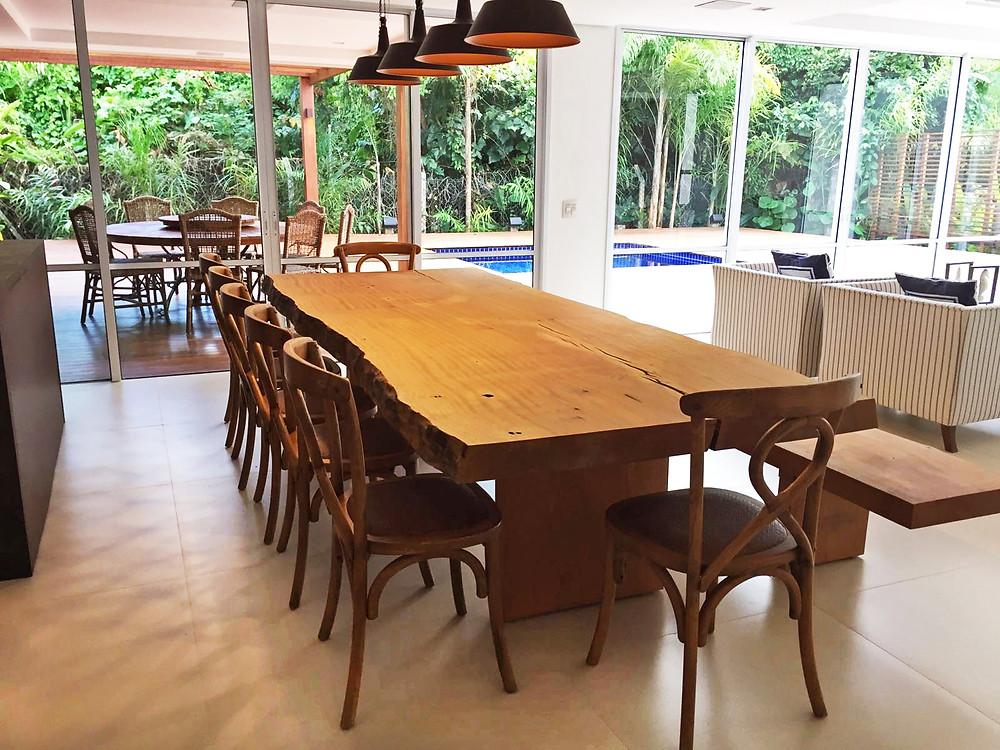 Mesa de jantar em madeira maciça em área churrasqueira próximo piscina